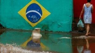 امرأة تسير في شارع غمرته مياه الأمطار الموسمية في ساو باولو في البرازيل في 11 آذار/مارس 2019