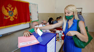 A woman wearing a face mask due to the ongoing coronavirus disease (COVID-19) outbreak casts her vote at a polling station during the general election in Podgorica, Montenegro August 30, 2020.