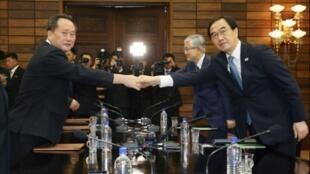 وزير شؤون التوحيد في كوريا الجنوبية شو ميونغ-غيون (يمين) مصافحا نظيره الكوري الشمالي ري سون غوون في بانمونجوم في 13 آب/أغسطس 2018