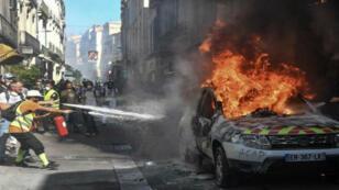 Un médico y varios manifestantes intentan apagar las llamas que consumieron a un automóvil de la Policía en Montpellier, Francia, el 7 de septiembre de 2019.