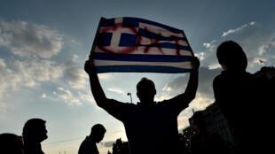 """Un manifestant anti-austérité brandit un drapeau grec barré du mot """"non"""", lors d'une manifestation à Athènes, le 29 juin."""