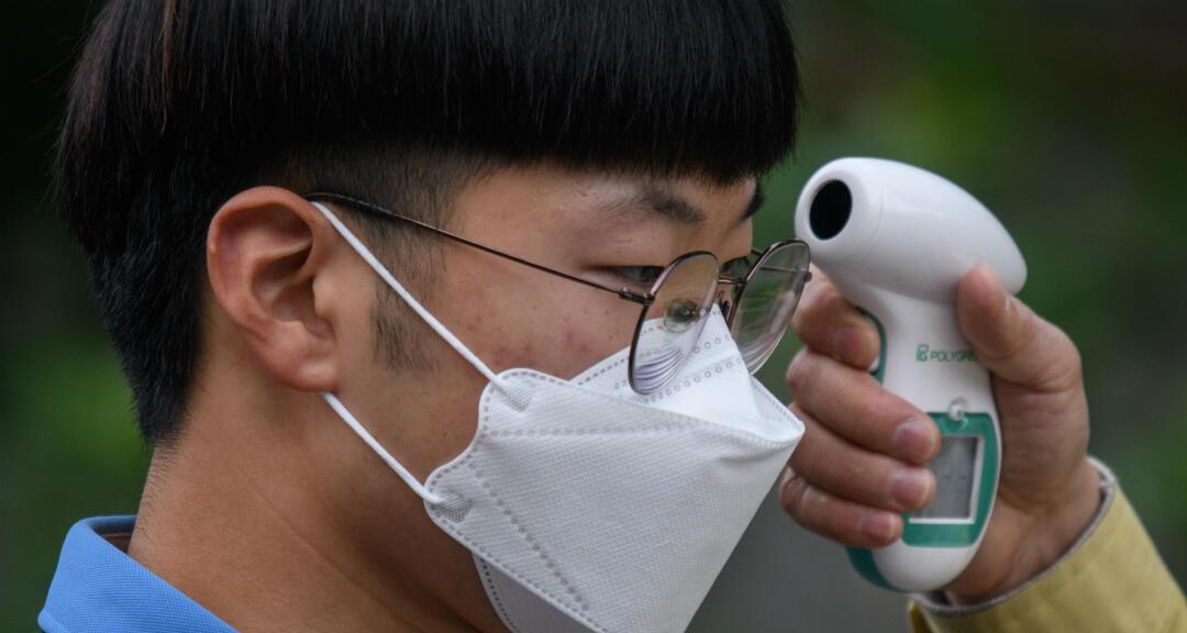Los estudiantes con mascarillas se someten a un control de temperatura cuando llegan a la Escuela Secundaria Keongbok en Seúl, el 20 de mayo de 2020.