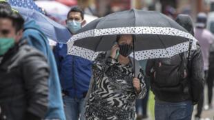 """Una mujer habla por teléfono mientras hace cola frente a una tienda durante el """"Viernes Negro"""" comercial, en Bogotá, el 19 de junio de 2020, en medio de la nueva pandemia de coronavirus."""