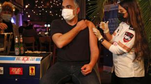 Una trabajadora sanitaria administra una dosis de la vacuna a un ciudadano israelí en un bar de Tel Aviv, el 18 de febrero de 2021