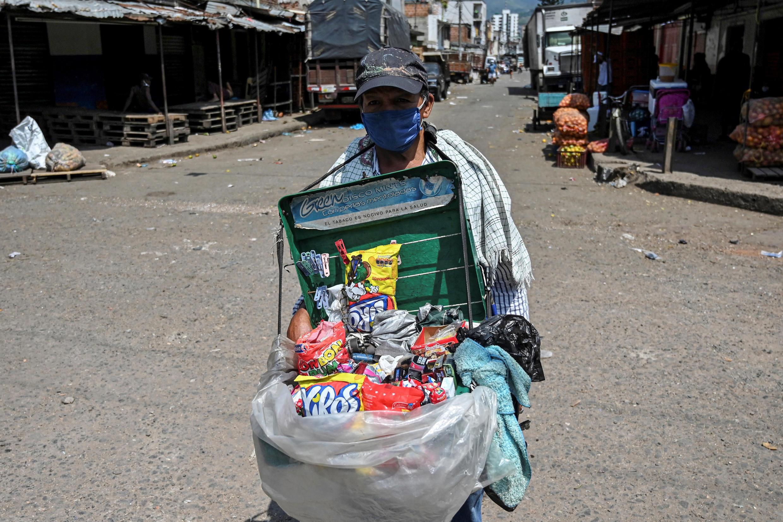 Un vendedor ambulante usa una máscara facial como medida preventiva contra la propagación del nuevo coronavirus COVID-19, en el mercado de Santa Elena en Cali, Colombia, el 15 de mayo de 2020.