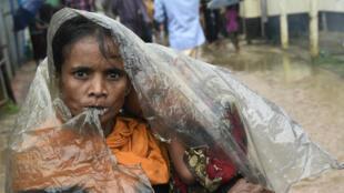 Un refugiado musulmán Rohingya se refugia de la lluvia en el campo de refugiados de Leda cerca del distrito de Bangladesh de Teknaf el 19 de septiembre de 2017.