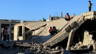 Des enfants glissent sur le toit d'un bâtiment effondré à Deraa, le 12 septembre, date d'entrée en vigueur d'une trêve dans toute la Syrie.
