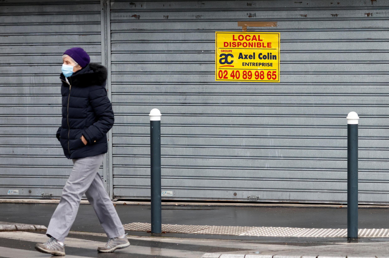 Una mujer, con una mascarilla protectora, pasa frente a un local comercial en alquiler en una calle de Nantes en medio del brote de Covid-19 en Francia, el 16 de febrero de 2021.