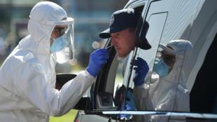 Un trabajador sanitario con indumentaria protectora toma una muestra de mucosa a un hombre en su automóvil para realizar una prueba de detección del coronavirus, el 30 de julio de 2020 en un área de servicio próxima a Ruhpolding, al sur de Alemania