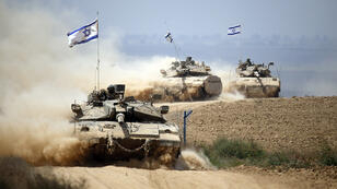 Israeli Merkava tanks roll near the border between Israel and the Gaza Strip on August 5, 2014