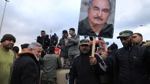People raise a picture of Libyan strongman Khalifa Haftar as they take part in a demonstration held by Libyans and Syrians in the eastern Libyan city of Benghazi to protest against Turkey's prospective military intervention in support of the UN-recognised Tripoli-based government, on January 3, 2020. (Photo by Abdullah DOMA / AFP)