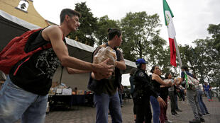 La gente pasa víveres en un centro de donación en el parque Lira en Ciudad de México el 20 de septiembre de 2017.