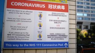 Un cartel escrito en inglés y en chino informa de los síntomas para identificar el coronavirus, fotografiado a las puertas del hospital St Thomas de Londres el 23 de marzo de 2020