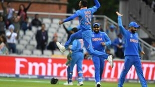 India's Hardik Pandya leaps into the air as he celebrates with teammates after the dismissal of Pakistan's Shoaib Malik