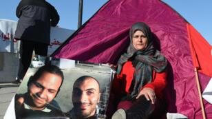 Sonia Rajab Ktari posant près des portraits de Sofiène (à droite) et Nadhir (à gauche), lors d'un sit-in en février 2016.