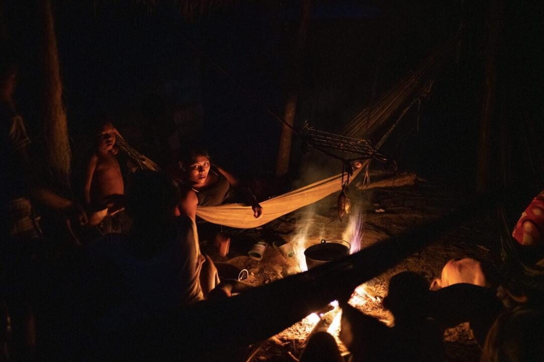 """Un grupo de indígenas Nukak prepara la cena en el fuego mientras descansan en sus hamacas. Los Nukak son un pueblo que permaneció como no contactado hasta 1988 y al que la Corte Constitucional declaró en """"riesgo de exterminio étnico y cultural"""". Aunque cuentan con un territorio de casi un millón de hectáreas, legalmente constituido como resguardo desde 1993, los Nukak han sido desplazados de manera forzada debido a las dinámicas de colonización, deforestación y cultivos ilícitos. Muchos se han visto obligados a asentarse en zonas urbanas en condiciones de extrema pobreza, como ellos, que viven en un lote a las afueras de San José del Guaviare."""