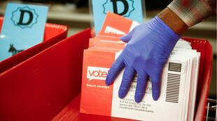 A worker wearing gloves places sorted Democratic Party ballots into containers during the presidential primary at King County Elections ballot processing center in Renton, Washington, on March 10, 2020.