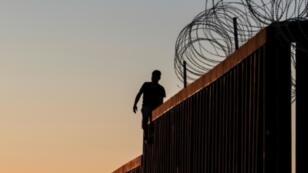 رجل يقف على جزء من الجدار الحدودي بين الولايات المتحدة والمكسيك في بلاياس دي تيخوانا بشمال غرب المكسيك- 18 نوفمبر/تشرين الثاني 2018 ا ف ب/ارشيف