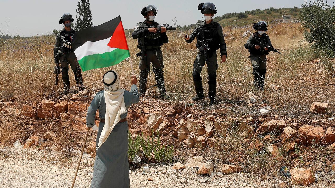 Un manifestant brandit un drapeau palestinien devant les forces israéliennes lors d'une manifestation contre le plan d'annexion de certaines parties de la Cisjordanie occupée, près de Tulkarem, le 5 juin 2020.
