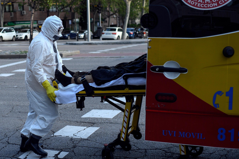 Un ambulancier de la protection civile de Madrid en tenue de protection transporte dans son véhicule un sans-abri soupçonné d'avoir été infecté par le Covid-19, à Madrid, le 11 avril 2020.