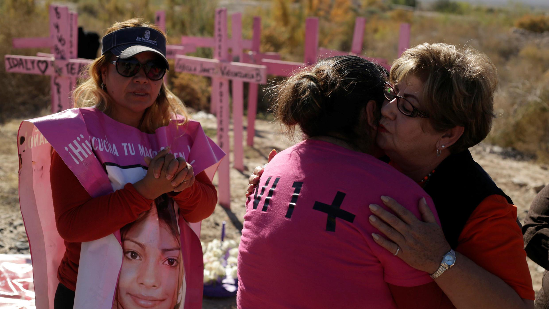 Familiares de mujeres desaparecidas reaccionan junto a cruces de madera en el arroyo El Navajo, donde se encontraron los cuerpos de varias mujeres, durante una ceremonia para conmemorar el Día Internacional para la Eliminación de la Violencia contra la Mujer en Praxedis G. Guerrero, en las afueras de Ciudad Juárez, México, el 24 de noviembre de 2017.