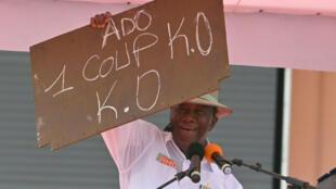 رئيس ساحل العاج الحسن اوتارا يحمل لافتة خلال تجمع لمناصريه في أبيدجان في 22 آب/أغسطس 2020