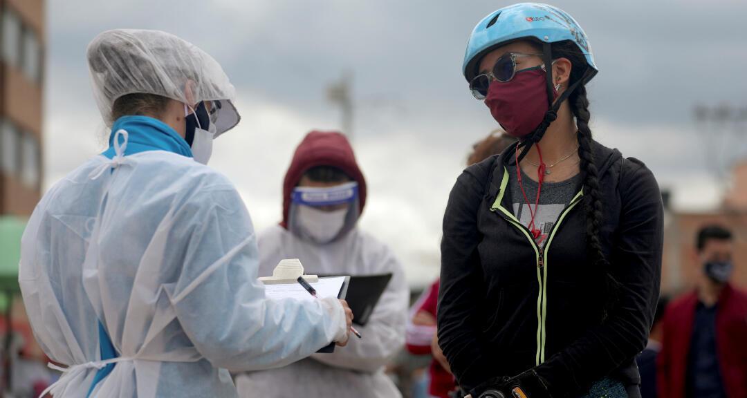 Una funcionaria del Ministerio de Salud usa equipo de protección para hablar con una mujer que se someterá a una prueba rápida de coronavirus en Bogotá, Colombia, el 1 de julio de 2020.