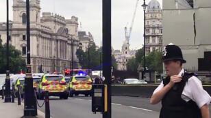 Capture d'écran d'une vidéo postée sur Twitter par @EwelinaUO montrant des policiers autour de la voiture qui a percuté une barrière de sécurité du Parlement britannique, le 14 août 2018