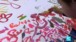 Des enfants dessinent devant le capitole, à Washington, pour demander l'arrêt des frappes turques en Syrie.