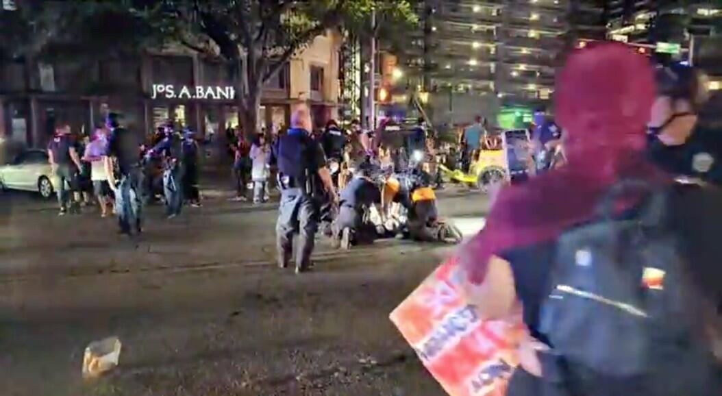 Policías y manifestantes alrededor de un hombre que recibió varios disparos, durante una protesta, en Austin, Texas, el 25 de julio de 2020.