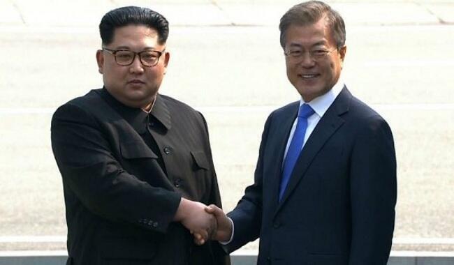 الرئيس الكوري الجنوبي مون جاي إن مصافحا الزعيم الكوري الشمالي كيم جونغ أون
