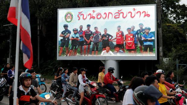"""""""Bienvenidos a casa, muchachos"""", se lee en un cartel con la fotografía de los niños atrapados en la cueva Tham Luang, en Chiang Rai, Tailandia."""
