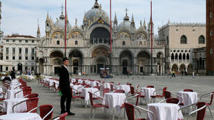 A waiter stands by empty tables outside a restaurant at St Mark's Square after the Italian government imposed a virtual lockdown on the north of Italy including Venice to try to contain a coronavirus outbreak, in Venice, Italy, March 9, 2020.