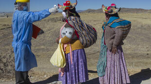 Un trabajador de la salud verifica la temperatura de dos mujeres residentes de las comunidades vecinas que se dirigen al mercado de alimentos semanal en Coata, a 40 km de Puno, Perú, cerca de la frontera con Bolivia, el 8 de julio de 2020.