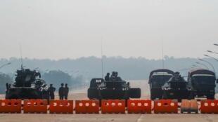 El Ejército de Myanmar monta guardia en un puesto de control con vehículos blindados que bloquean una carretera que conduce al edificio del Parlamento, en Naypyitaw, Myanmar, el martes 2 de febrero de 2021.
