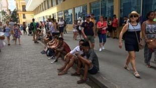 Cubains et touristes profitent de la zone wifi de la rue Obispo, à La Havane.