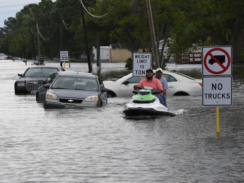 Deux hommes circulant en jet-ski à Crosby, au Texas, après les inondations provoquées par le passage de la tempête Harvey.