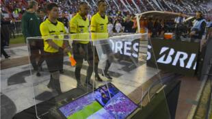 Des arbitres brésiliens devant le dispositif permettant l'arbitrage vidéo lors de la demi-finale de la Copa Libertadores, le 25 octobre 2017 à Buenos Aires.