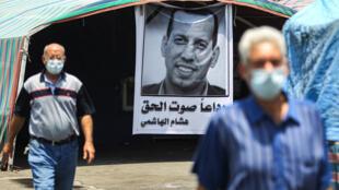 Men clad in masks due to the COVDI-19 coronavirus pandemic walk past a mourning tent bearing the poster of slain Iraqi jihadism expert Hisham al-Hashemi in Baghdad