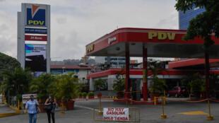 """Personas caminan frente a una estación de servicio cerrada, con el letrero """"No hay gasolina, solo tienda"""", en Caracas, el 14 de mayo de 2020"""