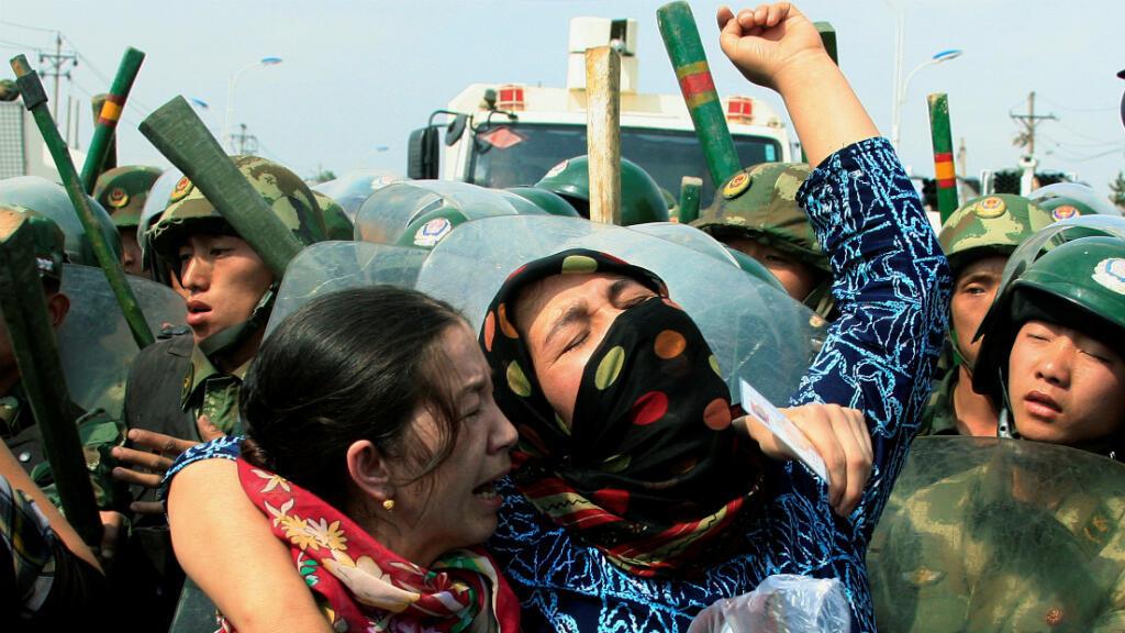 Foto de archivo de una mujer uigur que llora frente a la policía usando equipo antidisturbios cuando una multitud musulmana se enfrenta a las fuerzas de seguridad en la ciudad de Urumqi,  Región Autónoma de Xinjiang, en China, el 7 de julio de 2009.