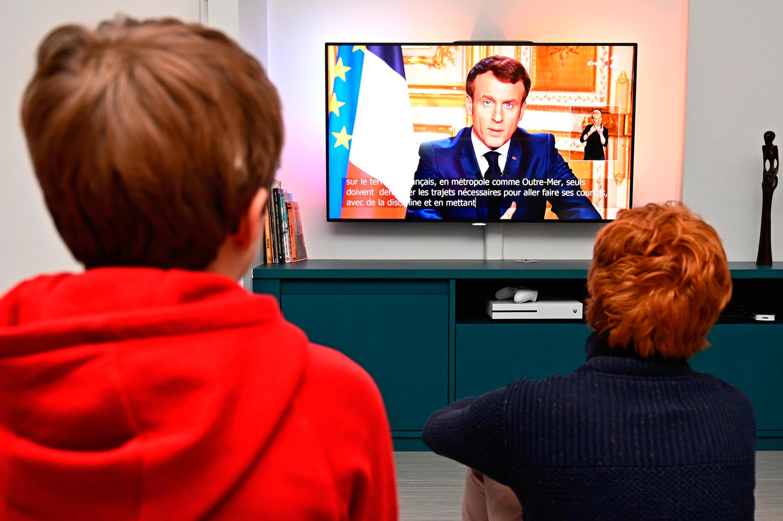 Children watch, on March 16, 2020 in Rennes, the speech of President Emmanuel Macron.