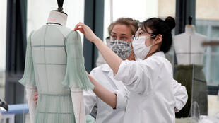 Dressmakers, wearing protective masks, pictured at the Dior fashion house workshop in Paris.