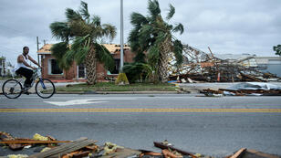 A man rides a bicycle past storm damage after Hurricane Michael in Panama City, Florida on October 10, 2018.