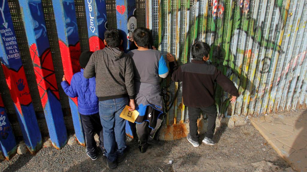 Archivo-Niños migrantes centroamericanos miran a través del costado del muro fronterizo en Tijuana, mientras se reúnen para celebrar la temporada navideña en Tijuana, México, el 14 de diciembre de 2019.