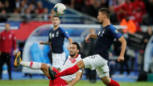 Soccer Football - Euro 2020 Qualifier - Group H - France v Turkey - Stade De France, Saint-Denis, France - October 14, 2019 Turkey's Hakan Calhanoglu in action with France's Clement Lenglet