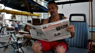 A man reads a slimmed-down edition of Cuban daily Granma in Havana, part of the country's first newspaper cut since 1990