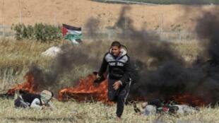 متظاهر فلسطيني يحاول الاحتماء خلال مواجهات مع قوات الأمن الإسرائيلية في 31 آذار/مارس 2018