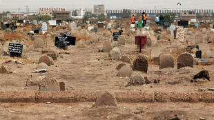 A picture taken on June 13, 2020, shows members of a forensic team at a cemetary, where a mass grave of conscripts killed in 1998 was discovered, in the Sahafa neighbourhood, south of the Sudanese capital Khartoum.