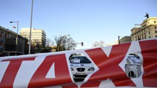 Banderole déployée lors la manifestation des chauffeurs de taxi, sur l'avenue Castellana à Madrid, le 27 janvier 2019.